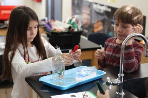 Two students play with vinegar and baking soda rocket.